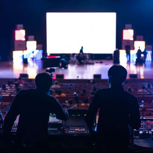Blur image of sound engineer team working to prepare for music concert stage.