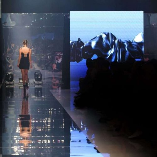 Black dress High heels Model walk back on mirror Runway Fashion Show catwalk with reflection on floor lighting along walk way, background stage ramp, copy space for text logo